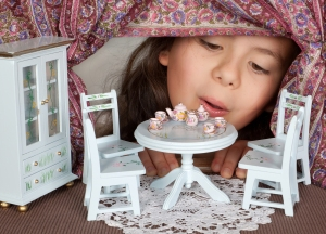 Little girl looking through a window into a doll's house like in